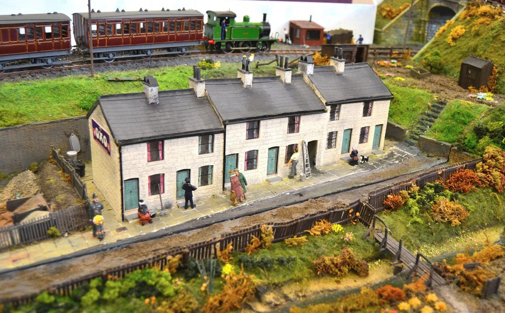 Railway worker's cottages, overlooked by a passing train.